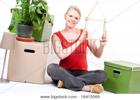 Young Woman With House Symbol Sits Between Move Cardboards And Plant