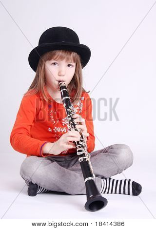 Little girl playing on a clarinet