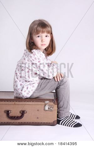 Little girl sitting on top of a suitcase