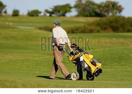 Jogador de golfe, andando com o carro de tração de golfe