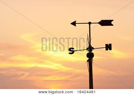 Silhouette of a weather vane over orange evening sky