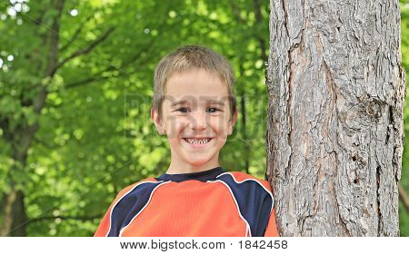 Boy Leaning Up Against A Tree