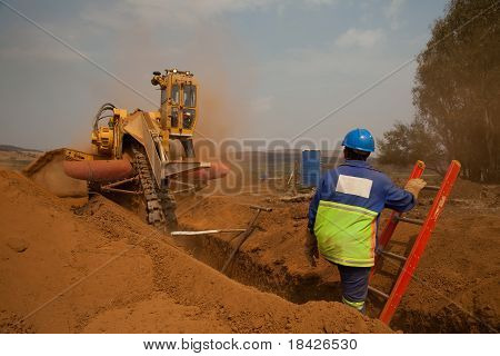 Worker On Ladder Watching Trencher Machine