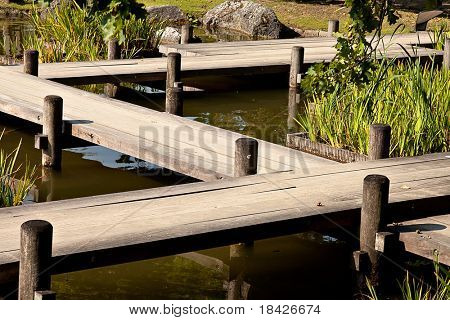 wooden bridge zigzagging a pond in Japanese garden