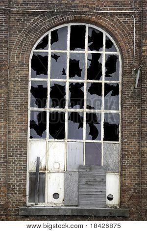 window in brick house with broken glass