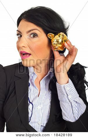 Surprised Woman Listening To Piggy Bank