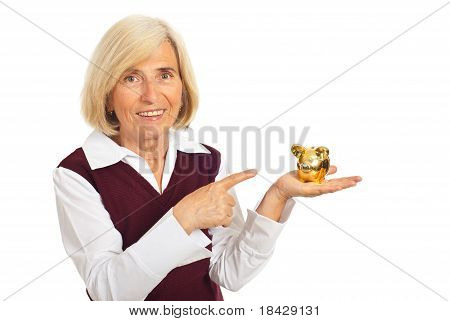 Happy Senior Woman Pointing To Piggy Bank