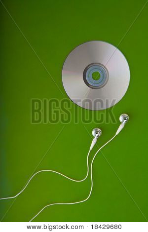 music CD with earphones headphones or earbuds on green background listening  songs on mp3 player white and silver phones for a portable radio