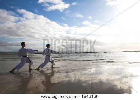 Men Practicing Karate On The Beach