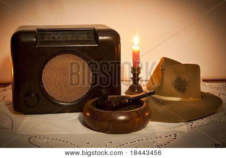 Old radio hat pipe and ashtray by candle light on table