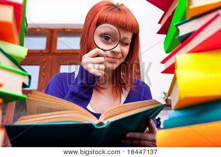 Teenager With Magnifier And Books