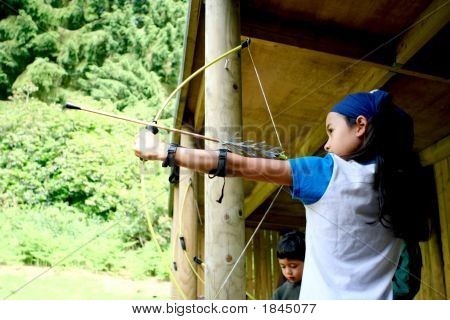 Young Girl Poised With Bow And Arrow
