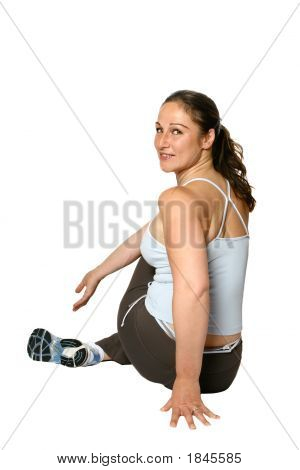 Fitness Trainer Half Turned Pushing Knee To Stretch Lower Back