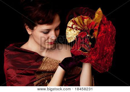 Artistic portrait of a beautiful woman, holding a red Carnival Mask