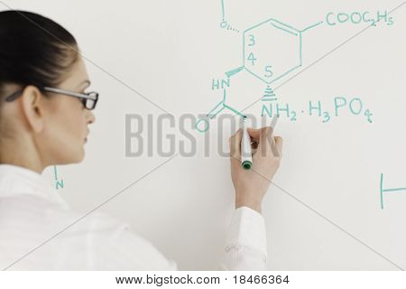 Dark-haired Scientist Woman Writing A Formula On A White Board