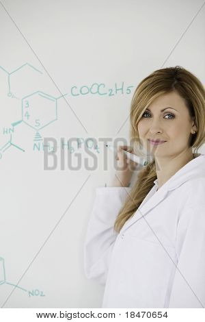 Cute Female Scientist Looking At The Camera While Writing A Formula