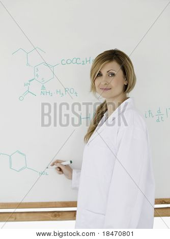Cute Scientist Looking At The Camera While Standing Near A White Board In A Lab