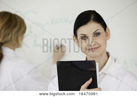 Blond-haired Scientist Writting A Formula Helped By Her Assistant