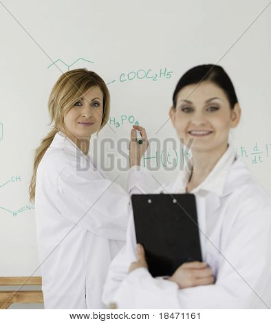 Young Scientist Writting A Formula Helped By Her Female Assistant