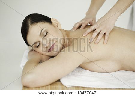Dark-haired woman relaxing while having a massage
