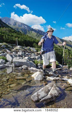 Hiker Crossing A River