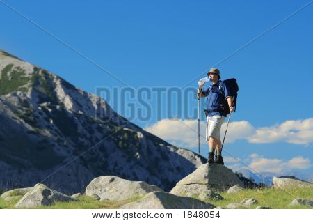 Backpacker Standing On A Rock In National Park Pirin