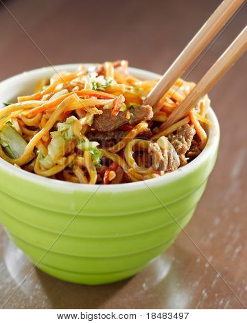 eating beef lo mein in a bowl with chopsticks