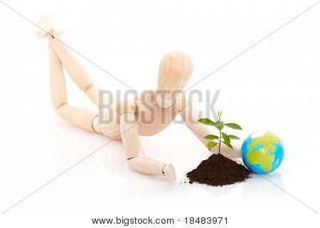 Fantoche olhando uma planta jovem ao lado de um globo da terra