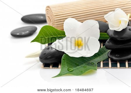 Frangipani flowers and leaves with zen stones on a bamboo mat