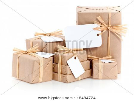 Closeup of parcels in brown wrapping paper and blank tags or labels isolated on white background