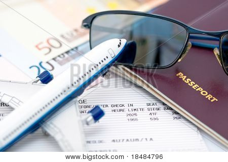 Closeup image with toy airplane, sunglasses,passport books, tickets and euro cash for travel concept