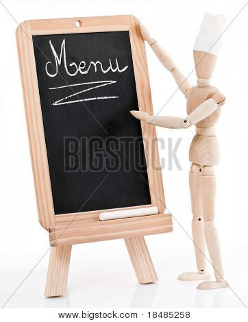 A wood figurine wearing a chef's hat, standing near a chalkboard with the word Menu on it.  White background