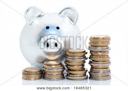 Stacks of Euro coins with piggy bank, isolated on white background