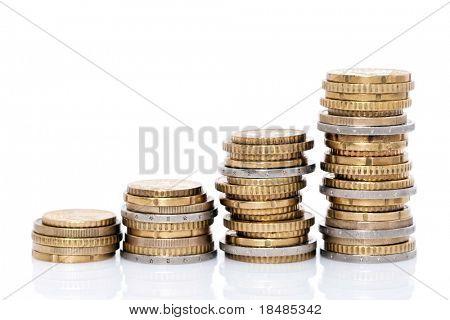 Vista lateral de pilas de monedas aumentando en altura, sobre fondo blanco de estudio