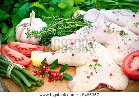Raw chicken meat portions with fresh seasoning ingredients on wooden board.