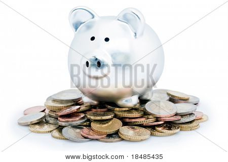 Silver piggy bank or money box on pile of silver Euro coins, isolated on white background.