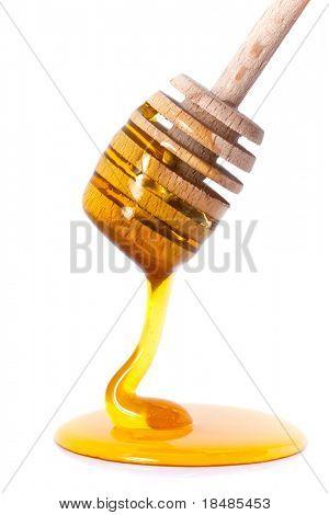 Honig tropft von einer hölzernen Honig-Zweischalen-Greifkorb auf weißem Hintergrund