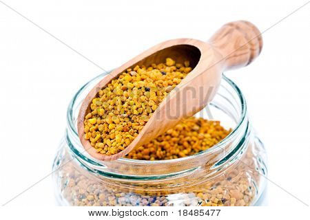 Closeup of a wooden scoop and a glass jar of bee pollen on white background