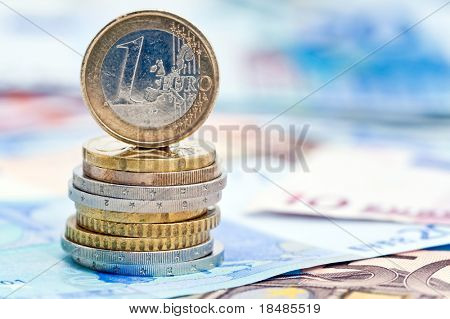 Euro coin balancing on stack with background of banknotes.