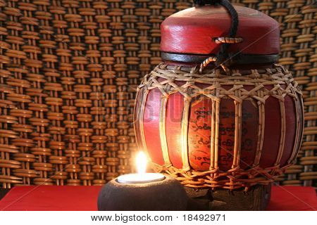 Old burmese jar with a lit candle. Taken at ISO 100 (lowest setting) to minimize noise.