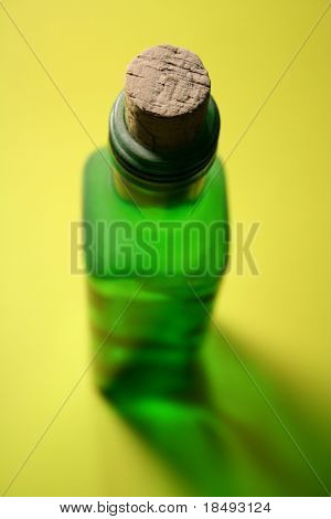 Green bottle with a cork attached with special lighting effect and shadow. Focus is on the cork.
