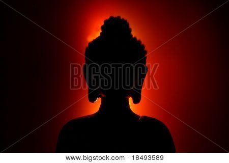 Silhouette of a Buddha with a red glow. Light painting technique.