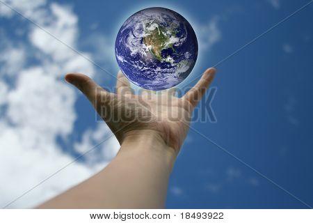 Mano tendida con una tierra brillante flotando por encima de. Concepto: El mundo en la palma de sus manos.