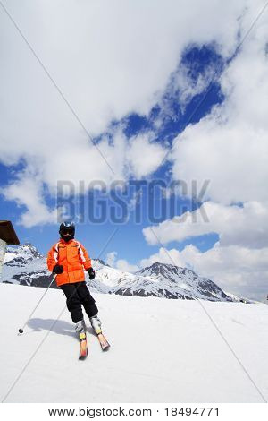 Skier in bright colored outfit skiing down a ski slope in the mountains during winter with blue cloudy skies in the background. Face not visible.