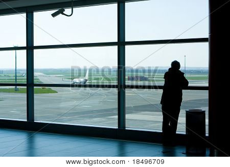 Airport lounge or waiting area with business man standing looking outside of window towards control tower