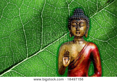 Golden buddha statue posing in zen and serene position against a nature background