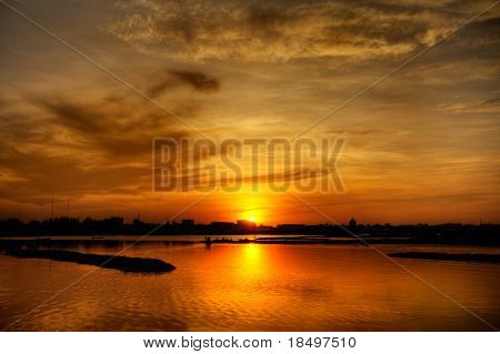 Hazy Asian sunset over lake in Cambodia