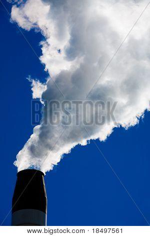 Schornstein spuckt Rauch aus ihm heraus mit blauer Himmel im Hintergrund