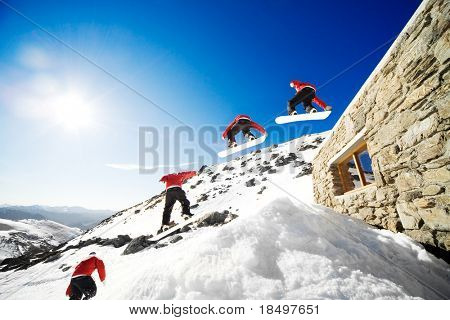 Sequence shot of snowboarder jumping off cabin roof