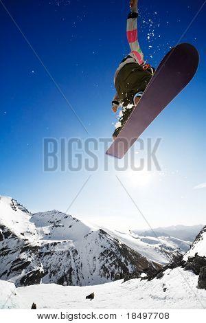 Snowboarder jumping through Air mit tief blauen Himmel im Hintergrund